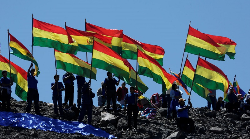 Bolivians hold national flags as they attend to watch the theatricalization of the battle of Canchas Blancas